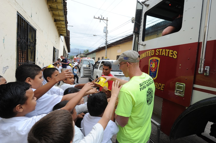 Staff Sgt. Gary Lorenz, 612th Air Base Squadron firefighter, hands out plastic firefighter hats to Honduran children during a fire prevention parade Oct. 19, 2011, at Comayagua, Honduras. The parade was followed by fire safety training for more than 95 local kindergarten children who were bused in to the 612th ABS's firehouse at nearby Soto Cano Air Base. (U.S. Air Force photo/Tech.Sgt. Matthew McGovern)
