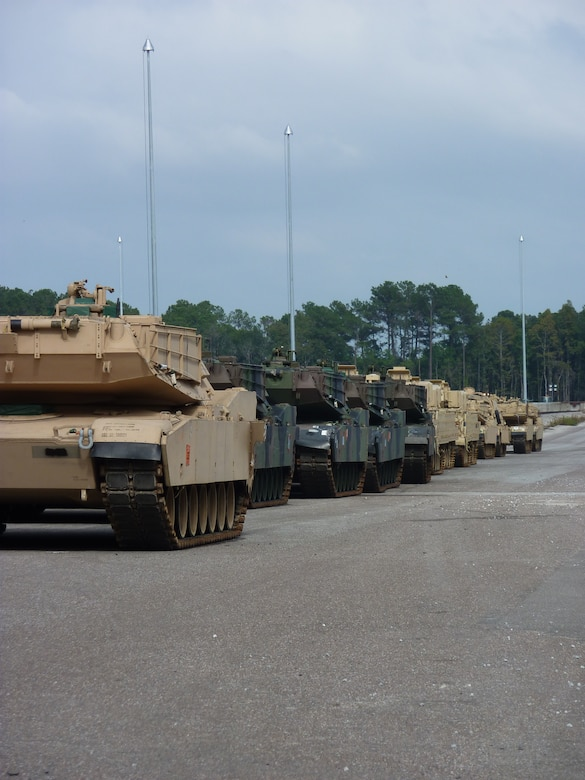 Track vehicles stage in preparation for loading onto railcars at Joint Base Charleston - Weapons Station, Oct. 21. The 841st Transportation Battalion, which is responsible for moving re-deploying cargo that is off-loaded at JB Charleston, loaded 44 track vehicles onto 22 railcars for shipment to multiple locations across the United States.The 841st is a subordinate unit of the Military Surface Deployment and Distribution Command and conducts surface deployment distribution and water terminal operations along the Atlantic Seaboard. (U.S. Army photo/Maj. Scott Hammond)