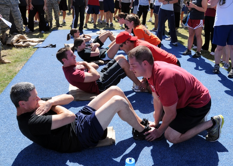 Col. Glen Baker, Commander of the 137th Air Refueling Wing, competes against his fellow wingmen during the push-ups and sit-ups competition. The base Olympics is one of the many events slated to occur on base being hosted and ran by the base mentorship program and the human resources advisors. For more mentorship program up-coming event information please call Master Sgt. Scherryl Coulter at 686-5276.   (U.S. Air Force Photo by Senior Airman Patricia Baker/Released)