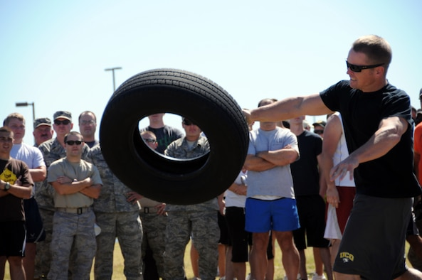 Tech. Sgt. Benjamin Cowart, assigned to the 137th Maintenance Group,  hurls a tire downrange in the tire toss competition during the base Olympics. One at a time, Cowart and other competitors had to find their own unique way of tossing the tire as far as they could.