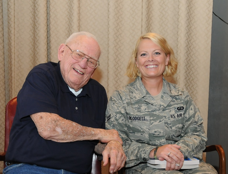 """Airman 1st Class Amanda Blodgett, 173rd Fighter Wing Finance, has her picture taken with Lynn """"Buck"""" Compton following the presentation August 32, 2011 at Kingsley Field, Klamath Falls, Ore.. She holds in her lap two books written by Compton and Malarkey respectively, recounting their experiences leading up to and during their days as Easy Company paratroopers. The two distinguished veterans happily signed books and took photographs with all who asked."""