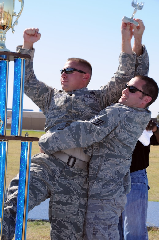 """U.S. Air Force guardsmen assigned to the 137th Maintenance Squadron celebrate a commanding victory in the 3 legged race held on base, Oct 1. """"This was one of the proudest moments of my career, said Staff Sgt Chris Howard. """"I would like to thank my partner Tech Sgt Slater for his continued support throughout the race."""" (U.S. Air Force Photo by Staff Sgt Caroline Hayworth/Released)"""