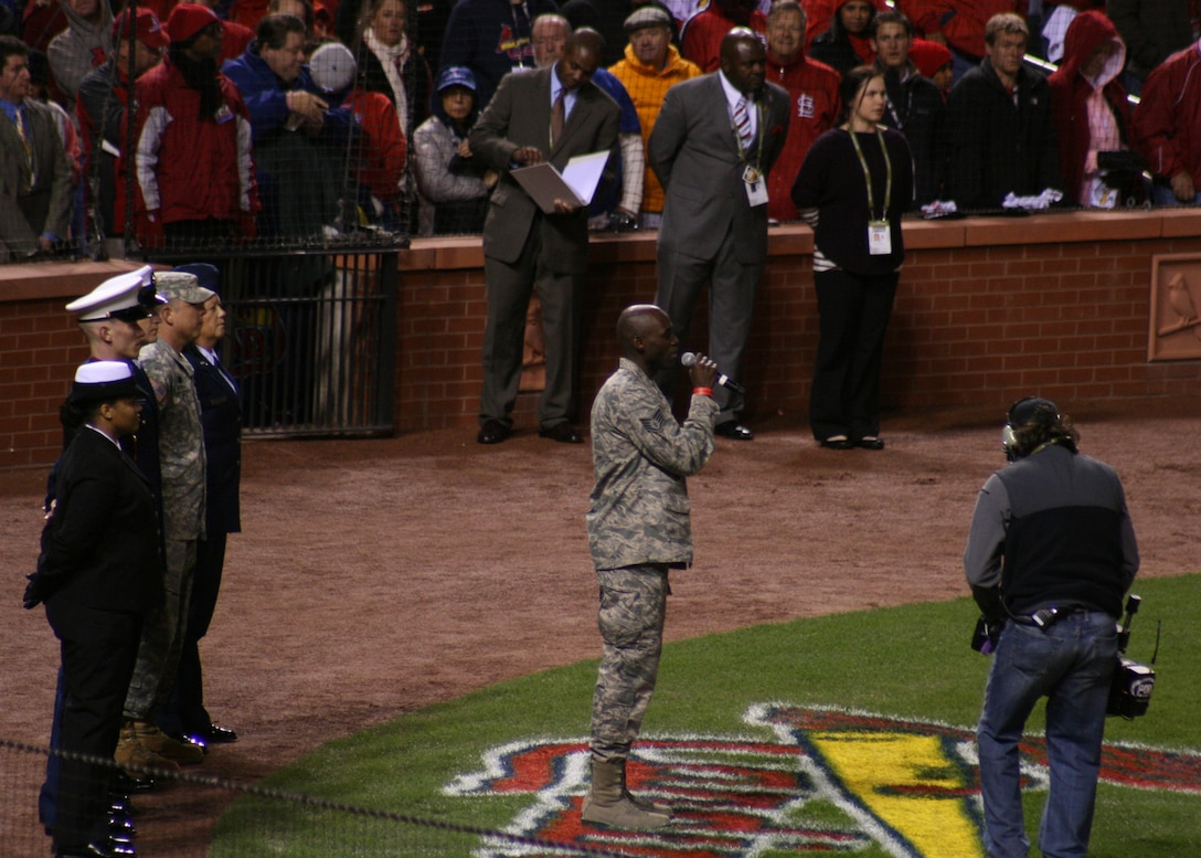 """Staff Sgt. Brian Owens, of the 571st Air National Guard Band of the Central States, sings """"God Blesss America"""" during the 7th inning stretch of Game 1 of the 2011 World Series at Busch Stadium, Oct 19.  The 571st is based at the 131st Bomb Wing, Lambert Air National Guard Base, Saint.Louis.  (Photo by Matthew J. Wilson)"""