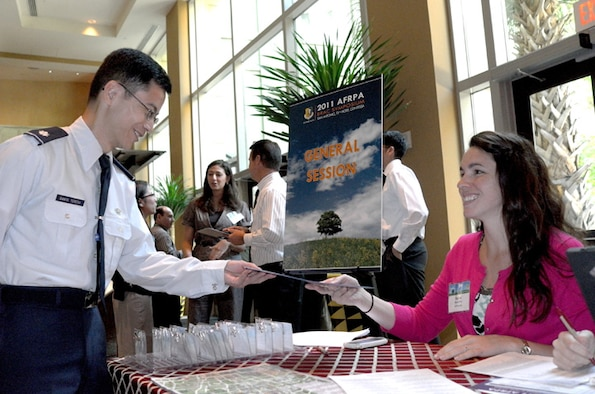 Lt. Col. J. Emmanuel I. Santa Teresa is greeted by Ms. Rachel Fish as he registers at the AFRPA 2011 BRAC Symposium in San Antonio, Texas. Lt. Col. Santa Teresa is deputy chief of environmental law at the Air Force Field Support Center based in San Antonio.