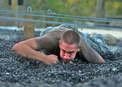 An Air Force Pararescue Trainee Low Crawls During Obstacle Course Event At The Lackland Training