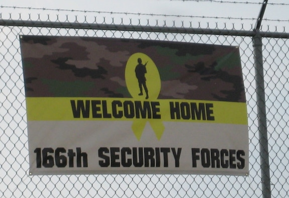 The welcome home sign created by a family member of one of 13 Airmen from the 166th Security Forces Squadron, Delaware Air National Guard, and the first sign that came into view on Oct. 21, 2011 as they were driven up Spruance Drive to enter the New Castle ANG Base, Del. after their arrival in the U.S. The Airmen completed a six-month combat-zone mission in Afghanistan in support of Operation Enduring Freedom. (U.S. Air Force photo/Tech. Sgt. Benjamin Matwey)