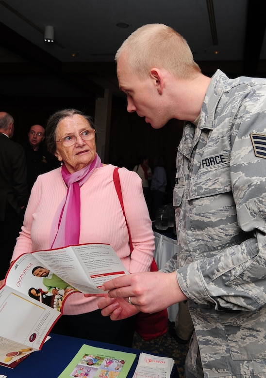 Air Force Staff Sgt. Anthony Eberly, 86th Aerospace Medicine Squadron, explains to retiree spouse Helga Campbell, the benefits offered at the Health and Wellness Center during a Retiree Appreciation Day Breakfast, Ramstein Air Base, Germany, Oct. 28, 2011. The event included briefs and stands set up by different organizations such as Service Credit Union, Optometry and Survivor Outreach Services. (U.S. Air Force photo by Senior Airman Brittany Perry)