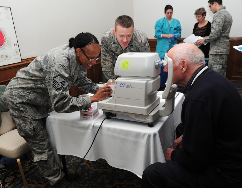Air Force Master Sgt. Constance Dangerfield and Capt. Jay Butler, 86th Aerospace Medicine Squadron, conduct an eye pressure screening on retired Army Command Sgt. Maj. Bruno Seewald during a Retiree Appreciation Day Breakfast, Ramstein Air Base, Germany, Oct. 28, 2011. The event included briefs and stands set up by different organizations such as Service Credit Union, Optometry and Survivor Outreach Services. (U.S. Air Force photo by Senior Airman Brittany Perry)
