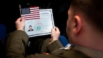 "LIBERTY ISLAND, N.Y.  -- Lance Cpl. Tomas Roginski examines his citizenship paperwork. at the conclusion of his naturalization ceremony, here, Oct. 28. Roginski was one of a few Marines, sailors, airmen, Coast Guardsmen and soldiers to join the naturalization ceremony with the group. The event was part of the day-long celebration of the 125th anniversary of the Statue of Liberty's dedication. The Department of Homeland Security rewards immigrants who join the military and serve honorably by exempting them from the normal residency requirements. Salazar told the new citizens, ""You are represent what is best about America, because you represent what Americans should be celebrating and standing for around the world. We are a nation of diversity, and that diversity strengthens our country."" Roginski immigrated to Brooklyn from Poland when he was a child. He currently serves in the Marine Corps with 6th Communication Battalion and is pursuing a degree in electrical engineering from the College of Staten Island. (Marine Corps production by Sgt. Randall. A. Clinton / RELEASED)"