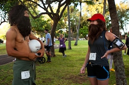 """Staff Sgt. Andres A. Trujillo, a U.S. Marine Corps Forces, Pacific Band member dressed as """"Cast Away"""" character Chuck Noland, meets another Tom Hanks impersonator, Sarah L. Mitson, an Oahu resident dressed as Forrest Gump, at the 2nd Annual General """"Howlin' Mad"""" Smith 5k here Oct. 29. Headquarters and Service Battalion, MarForPac, hosted the race as a fundraiser for the MarForPac birthday ball."""