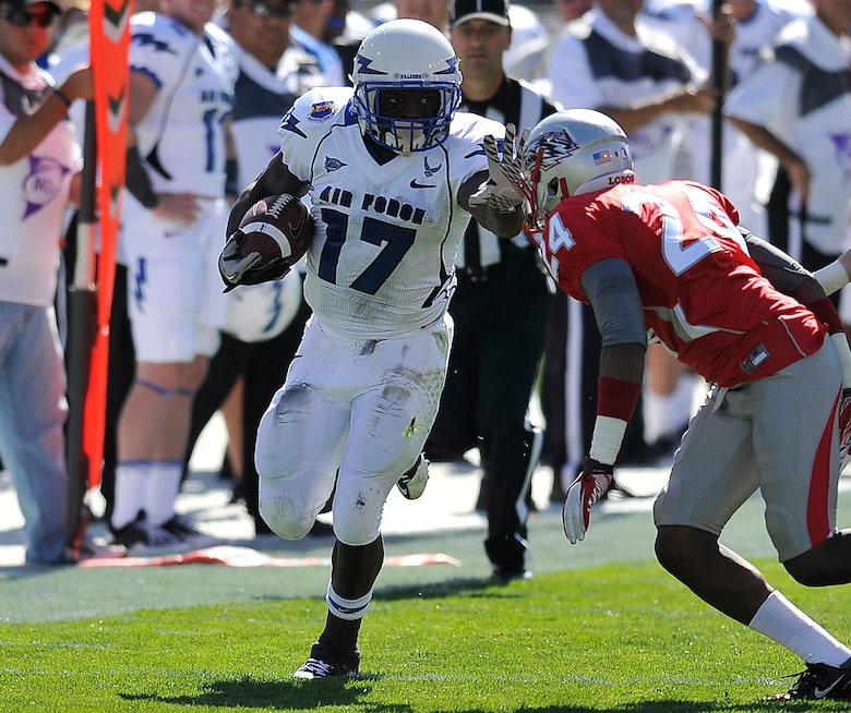 Air Force senior running back Asher Clark fends off New Mexico junior cornerback Destry Berry in the Air Force-New Mexico game in Albuquerque, N.M., Oct. 29, 2011. Clark carried 10 times for 77 yards, a key part of the Air Force's 335-yard rushing performance and 42-0 victory against New Mexico. (U.S. Air Force photo/Bill Evans)