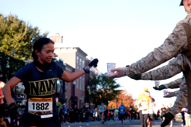 Anna Bernal receives water from a Marine at the 36th annual Marine Corps Marathon Oct. 30. Bernal finished with a time of 3:11:12 and was among 30,000 participants. Marines set up water and Gatorade stations along the route to refresh the runners.
