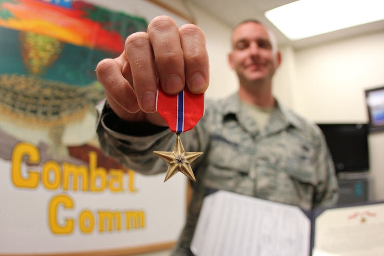 Staff Sgt. Stephen Herron reviews his Bronze Star medal and citation in the 52nd Combat Communications Squadron front office. Herron was presented the medal at a 689th Combat Communications Wing field commander's call, Oct. 31. Herron received the award for his efforts during his seven month deployment in support of forward deployed EOD teams. (U.S. Air Force photo/Robert A. Talenti)