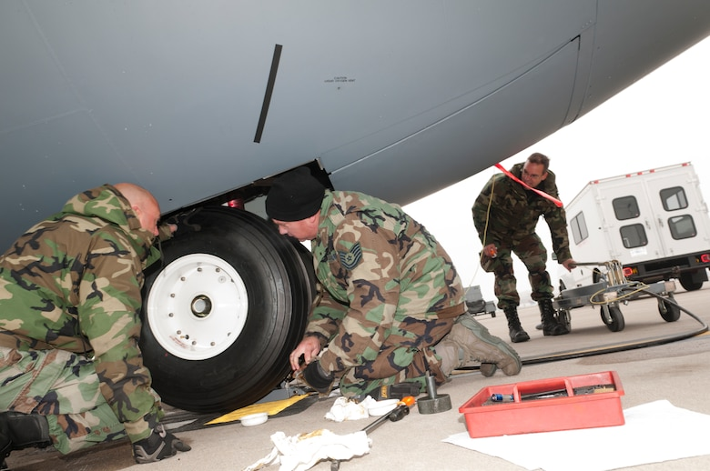 """Maintenance Airmen change a tire on a Minnesota Air National Guard C-130 """"Hercules"""" on the flightline at the Minneapolis – St. Paul international airport, on Oct. 31, 2011 wearing the Battle Dress Uniform on the last official day the Air Force allows BDUs to be worn. From left to right, Technical Sgt. Brad Dahl of the 133rd Maintenance Squadron, Technical Sgt. Dan Whitehead of the 133rd Aircraft Maintenance Squadron and Master Sgt. Tom Heckman, also from 133rd AMXS get the job done. USAF official photo by Senior Master Sgt. Mark Moss"""
