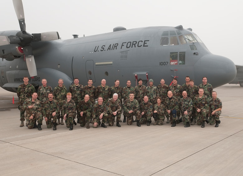 """Dozens of Airmen at the 133rd Airlift Wing wore their old Battle Dress Uniform to work on Oct. 31, 2011, which is the last official day members of the Air Force and Air National Guard can wear it. About 30 Minnesotans from units all around the base paused to celebrate the moment in front of a C-130 H3 """"Hercules"""" aircraft on the flightline of the air base on the Minneapolis – St. Paul international airport. USAF official photo by Master Sgt. Rick Crippen"""
