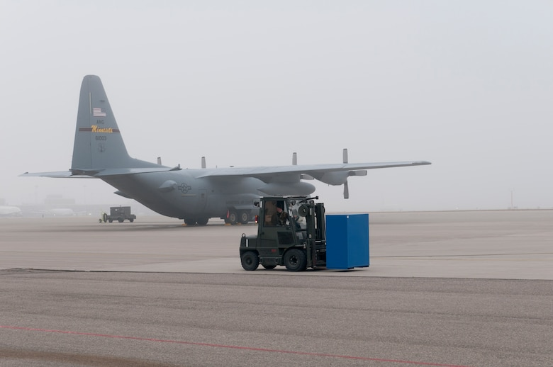 """As fog lifts above the flightline at the Minneapolis – St. Paul international airport, Technical Sgt. Eric Moan of the 133rd Aircraft Maintenance Squadron drives a forklift in front a Minnesota Air National Guard C-130 """"Hercules"""" on Oct. 31, 2011. Moan is one of dozens of Airmen on base wearing the Battle Dress Uniform on the last official day the Air Force allows BDUs to be worn. USAF official photo by Senior Master Sgt. Mark Moss"""