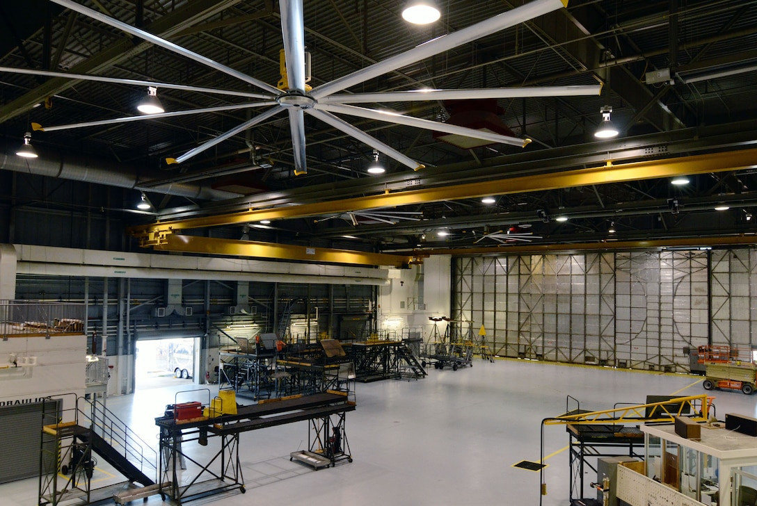 The Installation of large 24-foot ceiling fans provide aircraft maintenance personnel with seasonally comfortable air circulation throughout  hangar bay 3 in building 838 here Oct. 27. (U.S. Air Force photo/Don Peek)