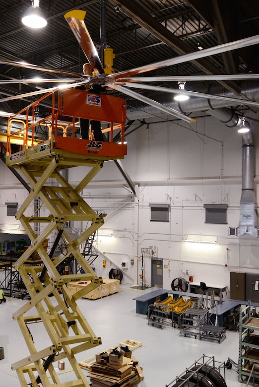 A member of the installation crew secures the fan blades of large 24-foot fans mounted on the ceiling of bay 3 in the maintenance hangar here Oct. 27. (U.S. Air Force photo/Don Peek)