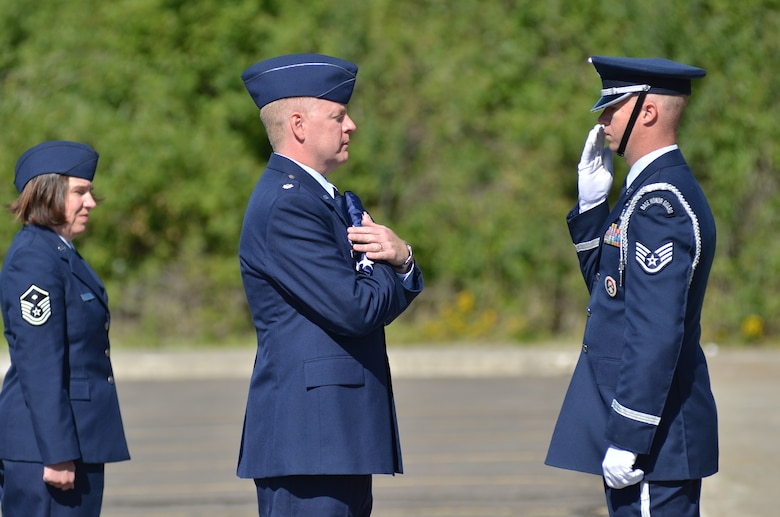 Lt. Col. Casey McGinn, commander of the 242 Combat Communications Squadron, receives the lowered flag from Staff Sgt. Johnny Enis of the 141st Air Refueling Wing Honor Guard.