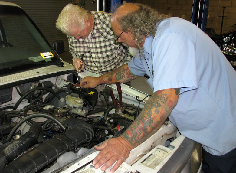 Jessie Mattox, Edwards Auto Hobby Shop supervisior, helps customer Dusty Rhodes, a retired NASA employee, troubleshoot a minor problem with the engine in Rhodes' 1995 Ford Ranger. (U.S. Air Force Photo by Diane Betzler)