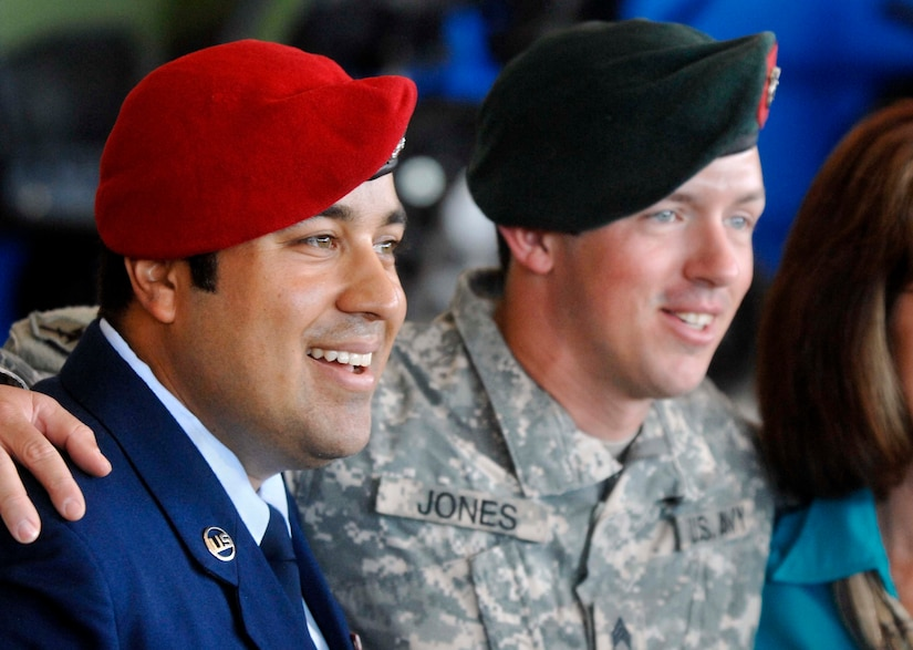 An airman and a soldier smile for a photo.
