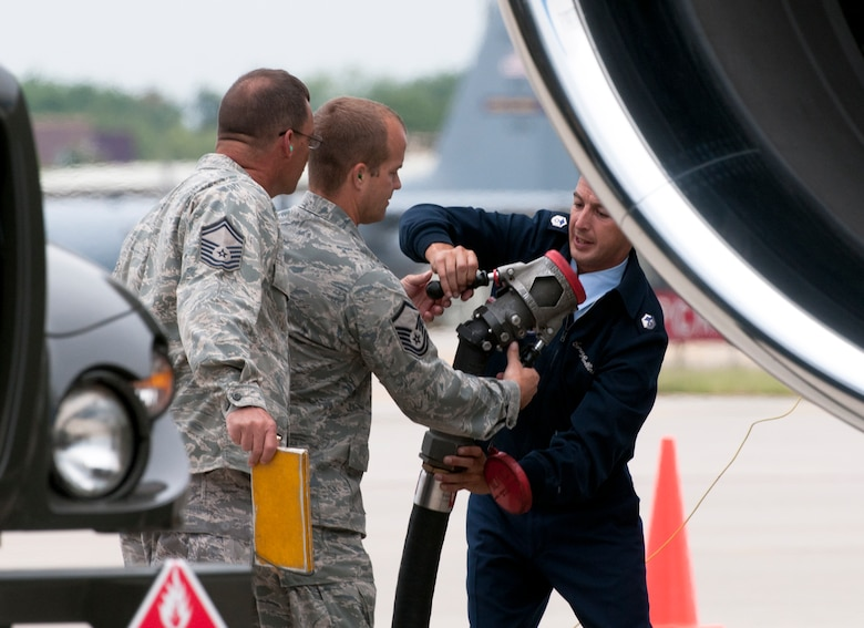 Under the wing of Air Force One at the Minneapolis-St. Paul International Airport on August 30, 2011, Senior Master Sgt. Steve Tuttle (left) and Master Sgt. Timothy Hayes of the 133rd Logistics Readiness Squadron hand the single point nozzle from the R11 refueler to the Air Force One crew chief so that he can attach it to the aircraft. Air Force One, the VC-25A which is a highly customized Boeing 747-200B, arrived at the Minnesota Air National Guard base bringing President Barack Obama, the commander-in-chief, to the Twin Cities where he delivered a speech to the American Legion Annual Conference. The visit is heavily supported with security, logistics, media and other support by the Airmen of the 133rd Airlift Wing. USAF official photo by Senior Master Sgt. Mark Moss