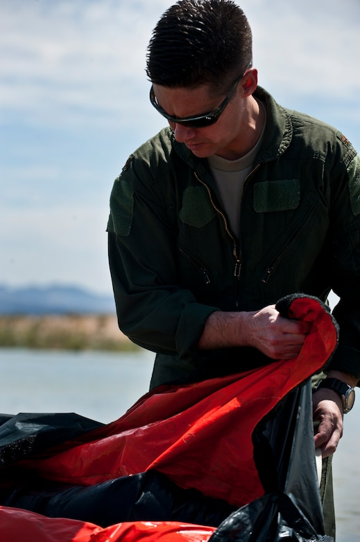 U.S. Air Force Maj. Jeff Cannon, 57th Weapons Support Squadron, F-15E Strike Eagle pilot, Nellis Air Force Base, Nev., pulls his life raft out of the water during a Survival, Evasion, Resistance and Escape water survival training course Aug. 17, 2011, at Lake Mead, Nev.  SERE specialists train high risk aircrew and personnel to survive, evade, and return safely should they eject, bailout, or otherwise become isolated during combat, anywhere in the world. (U.S. Air Force photo by Airman 1st Class George Goslin/Released)