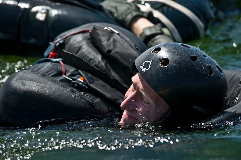 U.S. Air Force Capt. Justin Elliot, 422nd Test and Evaluation Squadron, F-15E Strike Division pilot, Nellis Air Force Base, Nev., pulls his raft while exiting the lake during the Survival, Evasion, Resistance and Escape water survival training course Aug. 17, 2011, at Lake Mead, Nev. SERE specialists train high risk aircrew and personnel to survive, evade, and return safely should they eject, bailout, or otherwise become isolated during combat, anywhere in the world. (U.S. Air Force photo by Airman 1st Class George Goslin/Released)