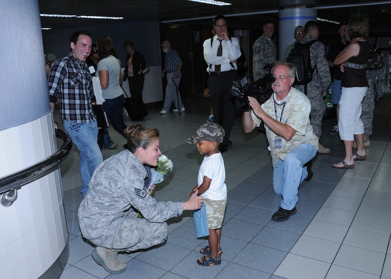 "Sidewinder vocalist Staff Sgt. Angie Johnson chats with a child of a band member while local news media looks on.  Members of Sidewinder returned to Saint Louis Sept 3 from their 45-day deployment to Southwest Asia where they performed for numerous troops in Iraq, Afghanistan, and throughout the region.  Sidewinder is the rock element of the 571st Air Force Band ""Air National Guard Band of the Central States"" based at the 131st Bomb Wing, Missouri Air National Guard, Lambert-Saint Louis.  Their rendition of ""Rolling in the Deep"" by Adele became a You Tube sensation and has been viewed over 1.3 million times.  (Photo by Master Sgt. Mary-Dale Amison)"