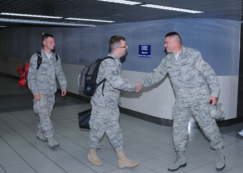 "Master Sgt. Scott Walker, 571st Air Force Band First Shirt, greets Sidewinder drummer Technical Sgt Kevin Maret and saxophonist Staff Sgt Toby Callaway as they arrive at Lambert Airport.  Members of Sidewinder returned to Saint Louis Sept 3 from their 45-day deployment to Southwest Asia where they performed for numerous troops in Iraq, Afghanistan, and throughout the region.  Sidewinder is the rock element of the 571st Air Force Band ""Air National Guard Band of the Central States"" based at the 131st Bomb Wing, Missouri Air National Guard, Lambert-Saint Louis.  Their rendition of ""Rolling in the Deep"" by Adele became a You Tube sensation and has been viewed over 1.3 million times.  (Photo by Master Sgt. Mary-Dale Amison)"