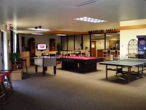 """Dayroom amenities include a 60"""" HD TV offering a wide selection of channels; another TV designated for gaming; and wireless internet, all at no cost to residents.  Billiards and table tennis are also available for the more traditional """"gamers."""""""