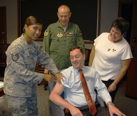 Dr. Steve Butler, Air Force Materiel Command executive director, received a flu shot Sept. 6 while AFMC Commander Gen. Donald Hoffman and his wife, Jackie, look on. The three gathered for their shots to help get spread the word that AFMC civilians will be offered flu shots in the coming the weeks. Mrs. Hoffman emphasized the importance of military family members getting their shots, as well. Dr. Butler's shot was administered by Technical Sgt. Victoria Gray of the 88th Medical Group at Wright-Patterson AFB. (U.S. Air Force photo/Ron Fry)