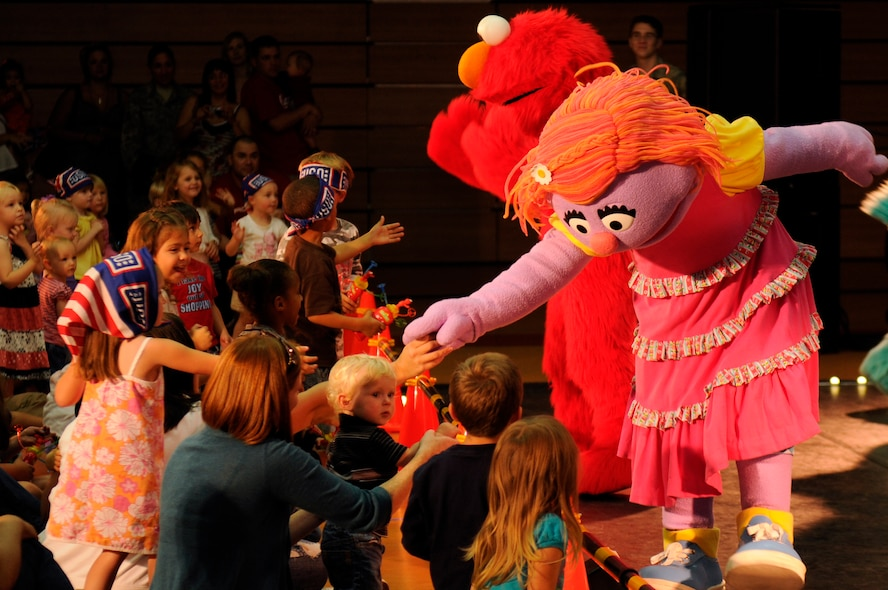 SPANGDAHLEM AIR BASE, Germany -- Katie, a new Sesame Street/USO character, and Elmo reach out to the crowd during the Sesame Street/USO Experience for Military Families tour here Sept. 2 Skelton Memorial Fitness Center . Elmo and his Sesame Street pals perform at installations all around the world. The tour focuses on the challenges families face during deployments. (U.S. Air Force photo/Airman 1st Class Brittney Frees)
