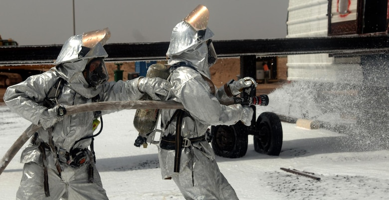 CAMP LEMONNIER, Djibouti -- Alfonso Bravo (left) and Siyaad Cheik, Camp Lemonnier Fire Department firefighters spray down a mock aircraft with AFFF foam concentrate during a training scenario, August 27. The Fire Department conducts routine training exercises to maintain skill proficiency. (U.S. Air Force photo by Senior Airman Jarad A. Denton)