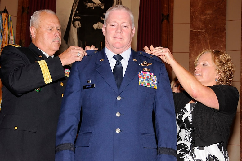 Maj. Gen. R. Martin Umbarger, The Adjutant General of Indiana, and Mrs. Mary Hauser pin a silver star on Brig. Gen. Jeffrey Hauser.  Photo by Master Sgt. John Day