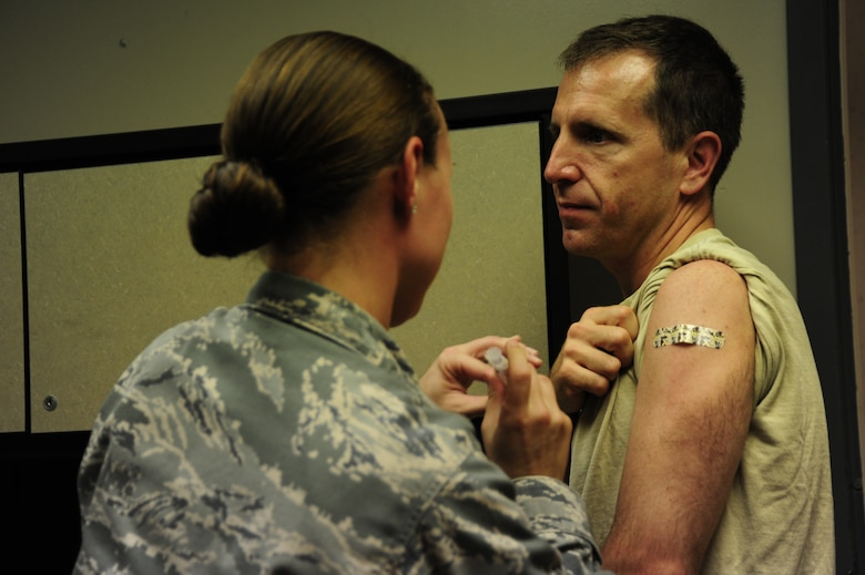 Col. James Slife, 1st Special Operations Wing commander receives a flu vaccination administered by Staff Sgt. Sheri Sellers, 1st Special Operations Medical Operations Squadron, at the medical group building at Hurlburt Field, Fla., Sept. 6, 2011.  Vaccinations are available at the clinic weekdays between 7:30 AM until 12:00 PM and 1:00 PM until 4:30 PM.  (U.S. Air Force photo by Amn Naomi M. Griego/ Released)