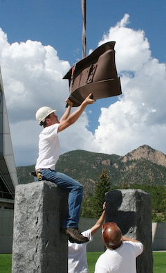 Workers lower a steel beam from the World Trade Center into position between two slabs of granite representing the Twin Towers in the Air Force Academy's Sept. 11 Memorial Aug. 24, 2011. The memorial is scheduled to be dedicated in a ceremony at the Academy Sept. 9. (U.S. Air Force photo/Paul Martin)
