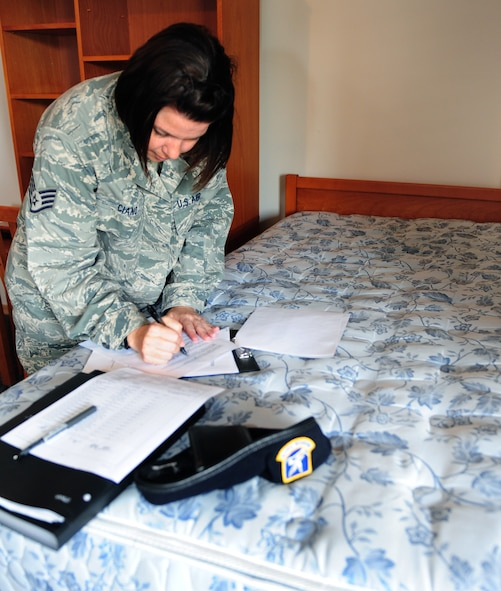 Staff Sgt. Rose Ciano, 39th Civil Engineer Squadron dorm manager, fills out a checklist during a final outprocessing room inspection for a member of the 39th Security Forces Squadron Sept. 7, 2011, at Incirlik Air Base, Turkey. Dorm managers conduct dormitory room inspections and unaccompanied housing inspections with people inprocessing and outprocessing the base. (U.S. Air Force photo by Senior Airman Anthony Sanchelli/Released)