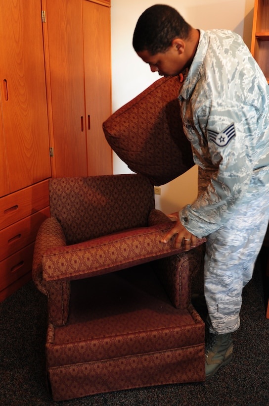 Staff Sgt. Marcus Pierce, 39th Civil Engineer Squadron dorm manager, checks for cleanliness underneath a chair cushion during a final outprocessing inspection in an Airman's dorm room Sept. 7, 2011, at Incirlik Air Base, Turkey. Dorm managers conduct dormitory room inspections and unaccompanied housing inspections with people inprocessing and outprocessing the base. (U.S. Air Force photo by Senior Airman Anthony Sanchelli/Released)