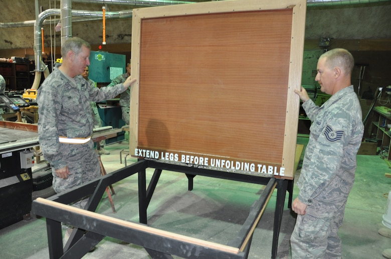 Colonel Michael Zick, 386th Air Expeditionary Wing commader recieves a brief from Technical Sgt. Steve Vernig, 386th Expeditionary Civil Engineer Squadron structural craftsman, on the flag table built for the folding and ironing of the American flag. (U.S. Air Force photo by Senior Airman Rachelle Elsea)