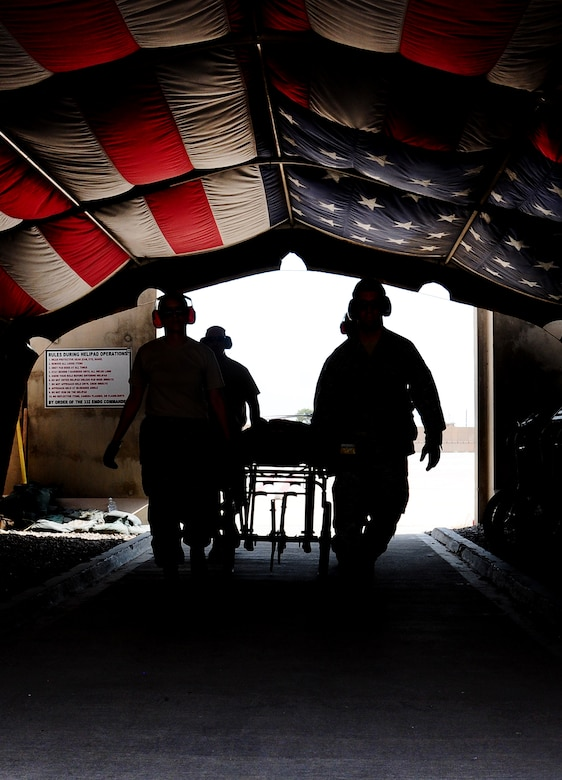 Airmen from the 332nd  Expeditionary Medical Group carry a stretcher under the Hero's Highway flag during  an aeromedical evacuation training exercise. The historical flag was recently cased in a cermony Sept. 1, 2011. (U.S. Air Force photo by Senior Airman Jeffrey Schultze)