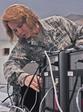 ANDERSEN AFB, Guam --Senior Master Sgt. Dawn Muskett, 644th Combat Communications Network Operations Flight superintendent, sets up a computer station at the elementary school here Sept. 9. Volunteers from the 644 CBCS visited Andersen Elementary School to setup a new computer lab and Smart Boards for students. (U.S. Air Force photo by Staff Sgt. Alexandre Montes)