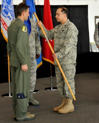 Lt. Col. Daniel Lapostole (right), incoming 129th Rescue Wing Maintenance Group Commander, receives the MXG guidon from Col. Steven J. Butow, 129th Rescue Wing Commander, during the 129th MXG change of command ceremony at Moffett Federal Airfield, Calif., Sept. 10, 2011. Lapostole formerly served as the 129th Rescue Squadron Commander. (Air National Guard photo by Staff Sgt. Kim Ramirez)