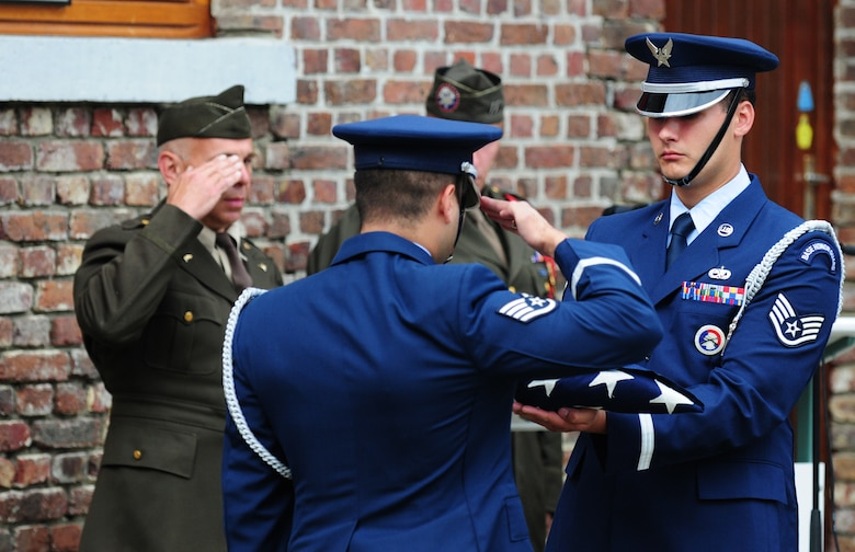 BORLO, Belgium – Staff Sgt. Victor Estupinan, 52nd Fighter Wing Honor Guard member, salutes the American Flag held by teammate Staff Sgt. Charles Lopez after performing a flag-folding ceremony during a Belgian 9-11 memorial ceremony here Sept. 11. U.S. service members and Belgian World War II Honor Guard Team members, along with the local community, participated in this ceremony as part of the Belgian Open Monument Day in remembrance of the victims of the Sept. 11, 2001 terrorist attacks on the United States. (U.S. Air Force photo/Airman 1st Class Matthew B. Fredericks)