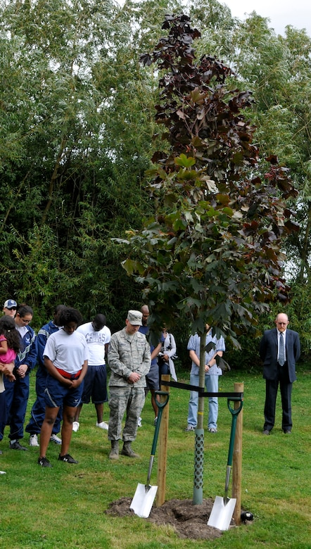 ROYAL AIR FORCE LAKENHEATH, England - Airmen and families bow heads for a moment of silence during a tree dedication ceremony to honor victims of 9/11 at Peacekeeper Park, Sept. 11, 2011. The tree dedication followed a 24-hour run that ended at 1:46 p.m. on Sept. 11, 2011, the time the first tower was hit. (U.S. Air Force photo by Senior Airman Tiffany M. Deuel)