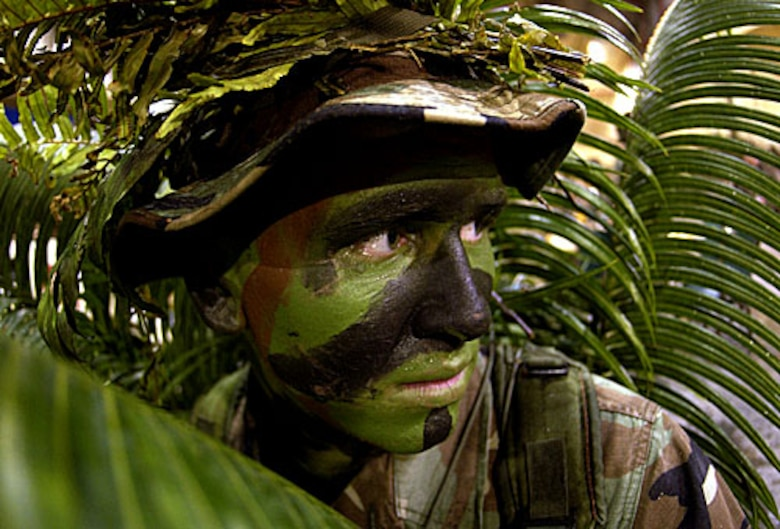 ANDERSON AIR FORCE BASE, Guam -- Airman 1st Class Nathan Fitzwater, a Fire and Emergency Services member from the 36th Civil Engineering Squadron, 36th Air Expeditionary Wing, Andersen Air Force Base, Guam, conceals himself by camouflaging in palm leaves and face paint during a Combat Dining In on Jan. 29, 2005. (U.S. Air Force photo/Staff Sgt. Bennie J. Davis III)