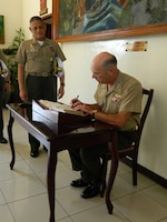 Lt. Gen. Duane D. Thiessen, commander of U.S. Marine Corps Forces, Pacific, signs the guest book as Maj. Gen. Rustico Guerrero, commandant of the Philippine Marine Corps, observes during Thiessen's visit to the Philippine Marine Corps headquarters, Sept. 14. Thiessen visited the Philippines to meet with the U.S. ambassador, U.S. and Filipino military officials, and component commanders from the Armed Forces of the Philippines.