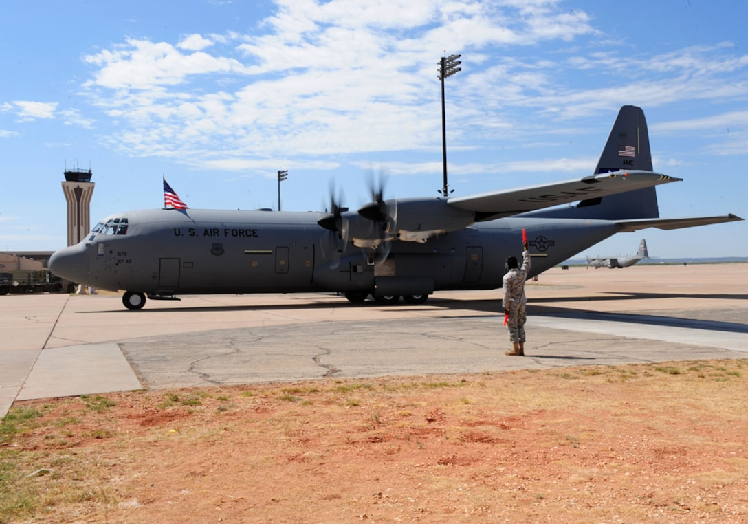 DYESS AIR FORCE BASE, Texas - A marshaller brings in the 317th Airlift Group's newest C-130J here Sept. 8. The delivery, by Lt. Gen. Robert R. Allardice, Commander, 18th Air Force, was the sixth in the 317th's continuing transition to the new aircraft. Dyess is slated to become home to the Air Force's largest C-130J fleet when it receives its 28th and final C-130J in 2013.
