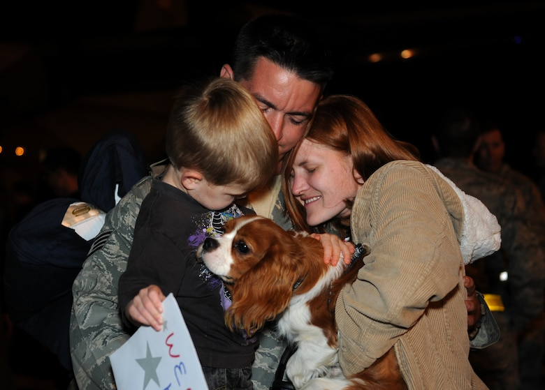 ROYAL AIR FORCE LAKENHEATH, England - Staff Sgt. Michael Prince, an electrical/environmental specialist with the 748th Aircraft Maintenance Squadron, hugs his wife, Staff Sgt. Ronda Prince, a supply manager with the 100th Logistics Readiness Squadron at RAF Mildenhall, his 3-year-old son, Aden, and their dog, Stuart, after returning from consecutive deployments Sept. 15, 2011. Approximately 60 Airmen from the 56th Rescue Squadron and 748th Aircraft Maintenance Squadron returned home after back-to-back deployments lasting more than nine months in support of Operations Enduring Freedom, Odyssey Dawn and Unified Protector. (U.S. Air Force photo by Airman Cory D. Payne)