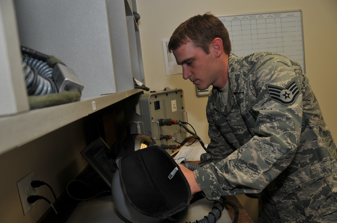 120th Fighter Wing Senior Airman Neil Kolve inspects a helmet during a post-flight check in the Aircrew Flight Equipment section on June 24, 2011. (U.S. Air Force photo by Senior Master Sgt. Eric Peterson.)